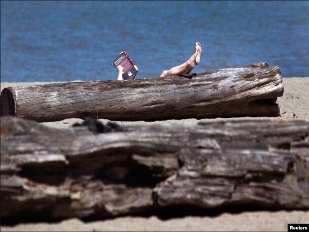 کولمبیا کے سمندر کنارے خاتون کتاب کا مطالعہ کرتے ہوئے