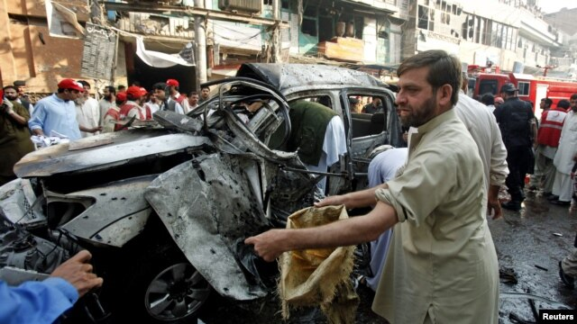 Security officers collect evidence from the site of a suicide bomb attack in Peshawar, November 7, 2012.