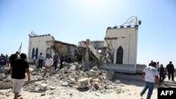 Quelques personnes se promènent à côté des débris d'un sanctuaire du soufisme détruit à Tajoura, dans la banlieue de Tripoli, Libye, 28 mars 2013.