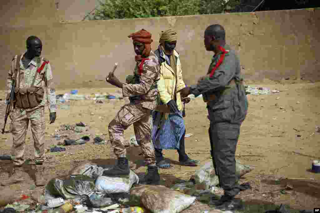 Malian soldiers inspect an explosive they found after residents notified authorities of suspicious bags left by radicals when they fled Gao, northern Mali, February 6, 2013.