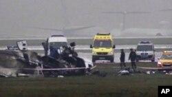 Nhân viên điều tra cạnh đống đổ nát của một chiếc máy bay phản lực tư nhân và một xe ủi tuyết tại sân bay Vnukovo ở Moscow, ngày 3/10/2014.