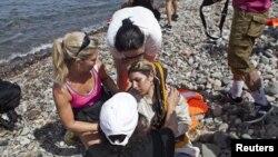 7일 그리스 동부 레스보스 섬에서 자원봉사자들이 소형 보트를 타고 해안가에 도착한 시리아 난민(가운데)을 돕고 있다.