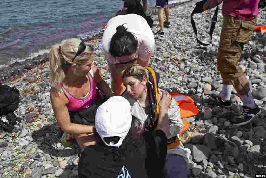 Volunteers help a Syrian refugee (C) who collapsed moments after arriving on a dinghy on the Greek island of Lesbos, Sept. 7, 2015.