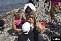 Yunanıstanın Lesbos adasında könüllülər Suriya qaçqınına yardım edirlər. 7 sentyabr 2015.