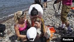 9月7日,救援人員在希臘萊斯沃斯島上救助一名暈倒的敘利亞難民。