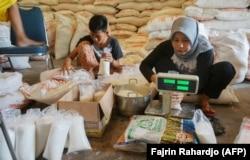 Penjual gula mengemas gula dalam kemasan yang lebih kecil sebelum dijual ke pelanggan di Tangerang, Banten pada 3 April 2020. (Foto: AFP/Fajrin Rahardjo)