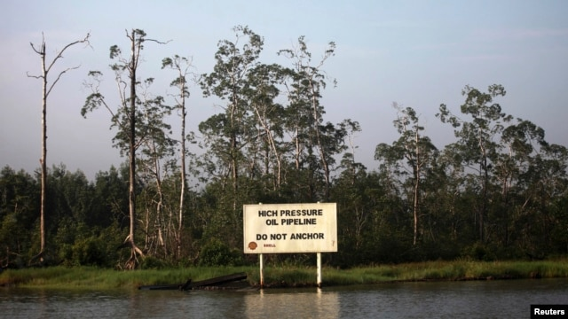 A warning sign belonging to the company Royal Dutch Shell is seen along the Nembe creek in Nigeria's oil state of Bayelsa, December 2, 2012 file photo.