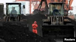 FILE - An employee walks between front-end loaders, which are used to move coal imported from North Korea at Dandong port in the Chinese border city of Dandong, Liaoning province Dec. 7, 2010.