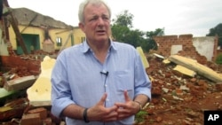 "FILE - U.N. humanitarian chief Stephen O'Brien answers reporters' questions during a trip to Bangassou, Central African Republic, July 18, 2017. O'Brien warned at the time of the growing violence; more than 300 people had been killed and 150,000 displaced since mid-May. He now says ""warning signs of genocide"" are present in the country."