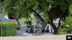 FILE - Police appear to setup a remotely operated robot during a stand off in Hutchins, Texas, June 13, 2015