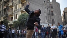 A protester throws stones at riot police during clashes at Tahrir square in Cairo November 26, 2012.