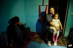FILE - Elnara, the wife of arrested Tatar protester Ali Asanov, is seen with one of her daughters in their home in Urozhayne, Crimea, Jan. 24, 2016. Russian authorities have used arrests as part of an intimidation campaign against local Tatars, rights advocates say.
