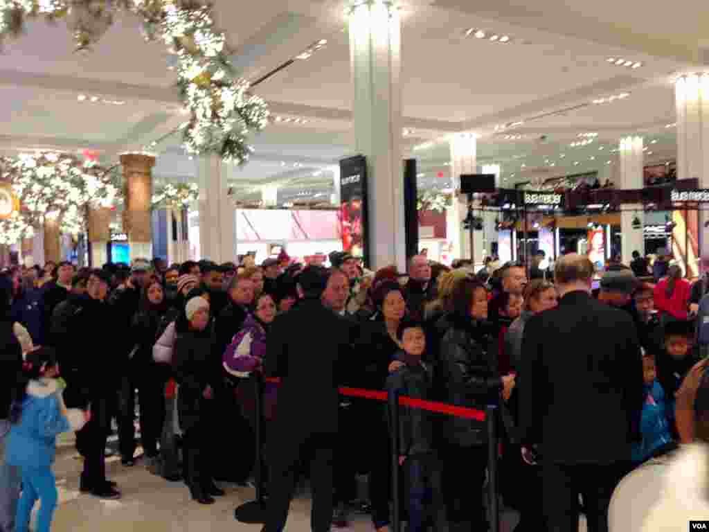 Shoppers line up to get on the escalator at Macy's Herald Square in New York on Thanksgiving, Nov. 28, 2013. (Sandra Lemaire/VOA)