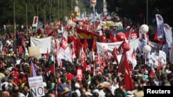 Demonstrators carry banners as they march to Madrid's Colon Square during a protest against government's cost-cutting measures, September 15, 2012.