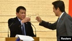 រូបឯកសារ៖ ប្រធានាធិបតីហ្វីលីពីន Rodrigo Duterte ជល់កែវជាមួយលោក Shinzo Abe នាយករដ្ឋមន្ត្រីជប៉ុន នៅគេហដ្ឋានរបស់លោក Abe នៅទីក្រុងតូក្យូ ប្រទេសជប៉ុន កាលពីឆ្នាំ២០១៦។