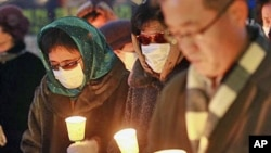 Former North Korean defectors, wearing masks to cover their identities, pay silent tribute during a rally for victims from North Korea's attack and freedom, human rights for North Korean, in Seoul, South Korea, December 20, 2010
