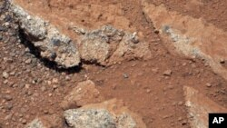 This image provided by NASA shows shows a Martian rock outcrop near the landing site of the rover Curiosity thought to be the site of an ancient streambed. Curiosity landed in a crater near Mars' equator on Aug. 5, 2012, on a two-year mission to study whe