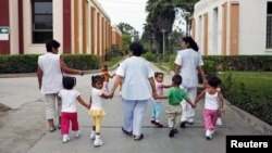 Children walk with social workers at the Puericultorio Perez Aranibar children's home in Lima, Peru, March 9, 2012.