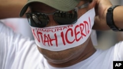 """A protester covers his face with headbands reading """"No to ICERD"""" during a rally to celebrate the government's decision not to ratify a U.N. anti-discrimination convention called ICERD at Independent Square in Kuala Lumpur, Malaysia, Dec. 8, 2018. ICERD stands for International Convention on the Elimination of All Forms of Racial Discrimination."""