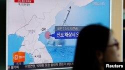 2016年7月9日,一名行人走过首尔一处地铁站的电视屏幕。电视正在播出朝鲜从东海岸港口新浦试射潜射导弹的新闻。
