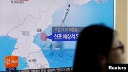 Một hành khách đi ngang qua màn hình tivi tại trạm xe lửa ở Seoul, Hàn Quốc, đang đưa tin vụ phóng tên lửa từ tầu ngầm của Bắc Triều Tiên, ngày 9 tháng 7 năm 2016.