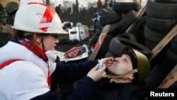 Tibbiyot xodimi Kiyevda jarohat olganlarga yordam berayapti. 21-fevral, 2014-yil.