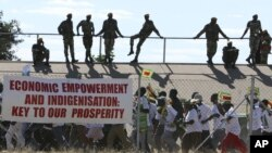 Zimbabwean soldiers look on as Zanu PF youths march for President Robert Mugabe at a rally in Bulawayo, June 20, 2008.