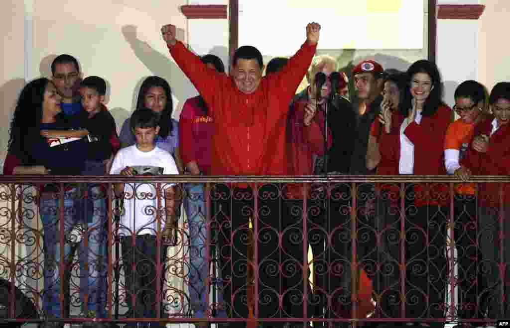 ທ່ານ Hugo Chavez (C) ຍົກມືສະແດງໄຊຊະນະ ຕໍ່ບັນດາຜູ້ສະໜັບສະໜຸນທ່ານ ຫລັງຈາກໄດ້ຮັບຂ່າວວ່າ ທ່ານໄດ້ຊະນະການເລືອກຕັ້ງ ຢູ່ນະຄອນຫລວງ Caracas.