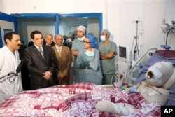 In this photo released 28 Dec 2010 by the Tunisian President's office, Tunisia's President Zine El Abidine Ben Ali, 2nd left, visits Mohamed Bouazizi, a young man who set himself on fire after police confiscated fruit and vegetables he sold without a perm
