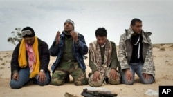 Libyan rebels pray in the desert in front a weapon on the frontline near Sultan, south of Benghazi, March 18, 2011