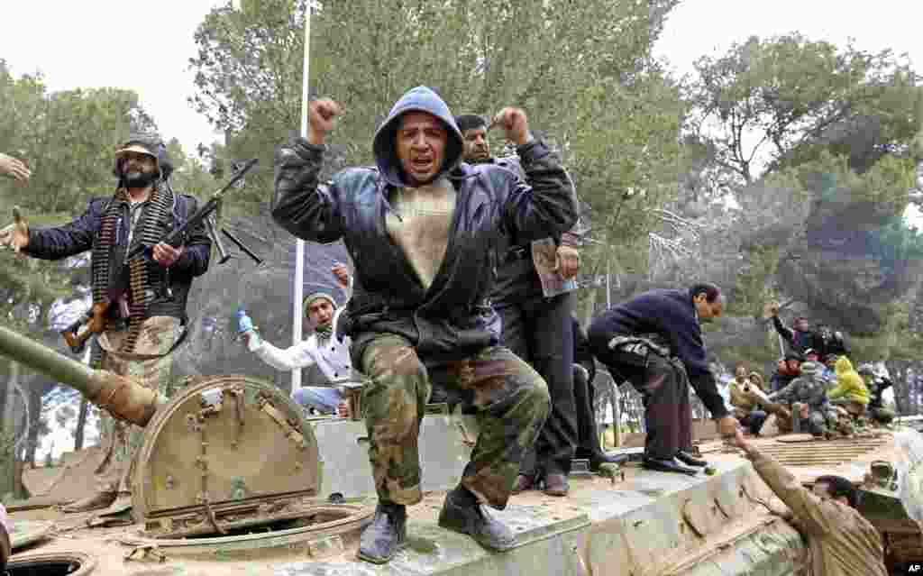 People celebrate on an army armored vehicle in the eastern Libyan town of Shahat,February 24, 2011. (Reuters Image)