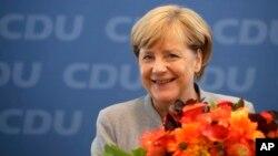 លោកស្រីអធិការបតីអាល្លឺម៉ង់ Angela Merkel ញញឹមមុនពេលកិច្ចប្រជុំរបស់គណបក្ស Christian Democratic Union (CDU) របស់លោកស្រីកាលពីថ្ងៃទី២៥ ខែកញ្ញ នៅទីក្រុងប៊ែឡាំង។ លោកស្រីបានជាប់ឆ្នោតក្នុងអាណត្តិទី៤របស់លោកស្រី។