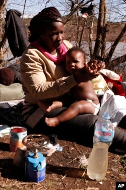 FILE - Sandrine Koffi washes her 10-months-old daughter Kendra with river water during a rest near the village of Marvintsi, Macedonia, March 3, 2015.