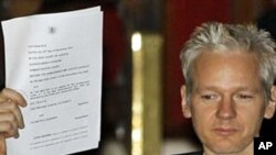 WikiLeaks founder Julian Assange holds up a court document for the media after he was released on bail, outside the High Court, London, 16 Dec 2010