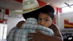 FILE - Miguel, 3, clings to his father, Miguel, an undocumented migrant, in San Juan, Texas, Aug. 27, 2010. Miguel and his wife, who remain in the U.S. as undocumented migrants, have two children born in the U.S.