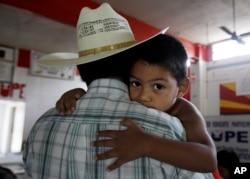 Un pequeño se aferra a su padre, un inmigrante ilegal en San Juan, Texas, Aug. 27, 2010. El niño y un hermano son ciudadanos estadounidenses por nacimiento.