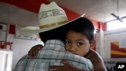 三歲的米古爾緊緊摟著他的父親。他的父母是非法移民,因為兒子米古爾出生在美國德克薩斯州而留在美國。(資料照片)