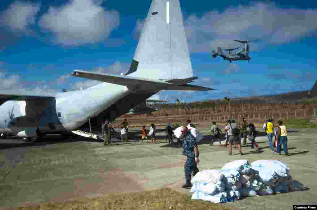 Philippine citizens board an HC-130 Hercules from the 3 Marine Expeditionary Brigade (3 MEB) as Sailors assigned to the U.S. Navy's forward-deployed aircraft carrier USS George Washington (CVN 73) transport relief supplies in support of Operation Damayan.