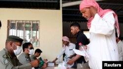 Petugas imigrasi Arab Saudi di Alisha, Riyadh sebelah barat, melayani pekerja imigran ilegal yang mengurus dokumen pemutihan izin tinggal (26/5). (Reuters/Faisal Al Nasser)