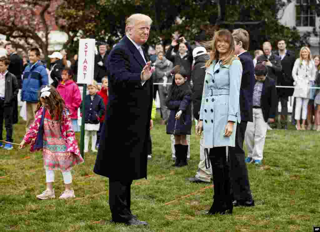 President Donald Trump and first lady Melania Trump turn to the crowd at the annual White House Easter Egg Roll, April 2, 2018.