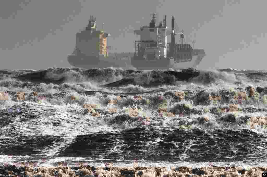 Two tankers are battered by gale winds in the rough waters of the Gulf of Cagliari, Sardinia, Italy, Nov. 18, 2013.