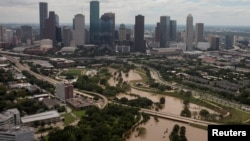 The Houston skyline is seen in the background as Buffalo Bayou is floods from Tropical Storm Harvey in Texas, Aug. 30, 2017.