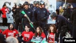 Polisi bersiap menahan demonstran yang menyerukan upah minimum US$15 per jam dalam demonstrasi di Los Angeles, California (29/11). (Reuters/Lucy Nicholson)
