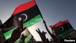 Libyans celebrate on the streets in Tripoli's Martyrs' Square after casting their vote during the National Assembly election, July 7, 2012.