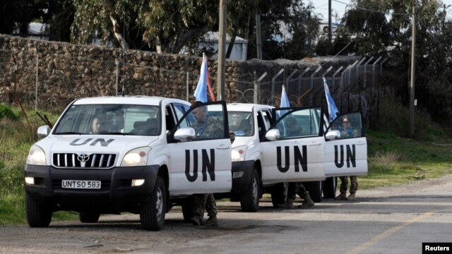 United Nations peacekeepers put on protective gear before driving through the Kuneitra border crossing between Israel and Syria, in the Israeli occupied Golan Heights, March 8, 2013.
