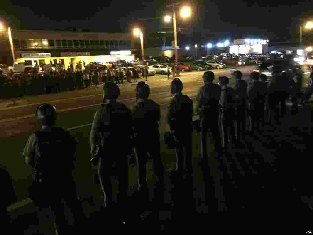 Cảnh sát và người biểu tình tập trung tại West Flourissant, Ferguson, ngày 10 tháng 8 năm 2015. (Kane Farabaugh/VOA News)