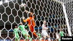Alman Andre Schuerrle make yon gòl kont gadyen aljeryen an, Rais Mbolhi, nan peryòd pwolongasyon match ant 2 ekip yo(Foto 30 jen, 2014).