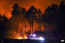 Kendaraan sherif terlihat melintas di sepanjang Highway 98 di Walton County, Florida, saat terjadi kebakaran, Rabu malam, 6 Mei 2020.