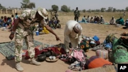 FILE- Soldiers guard people fleeing from Boko Haram's carnage, Dec. 8, 2015. People detained by the military and a civilian self-defense force are disappearing in northeast Nigeria some wrongly accused of fighting for Boko Haram.