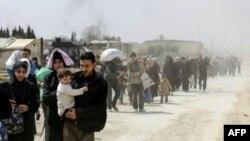 Des civils fuient la région de Hammouriyé dans l'enclave rebelle de la Ghouta orientale, après environ un mois de bombardements du régime syrien, le 15 mars 2018